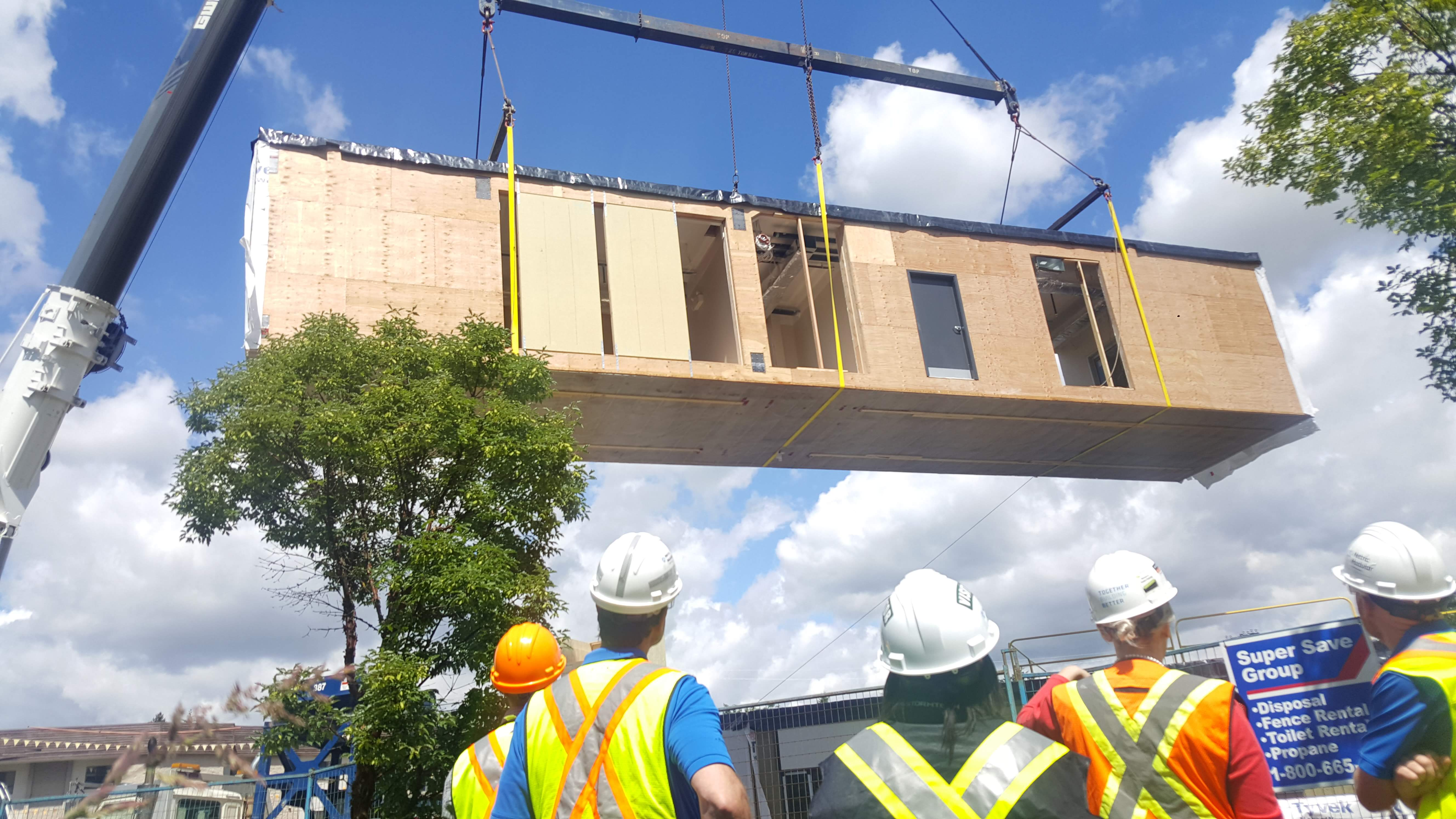 Workers look on as a crane operator lifts a prefabricated section of a new 220-bed dormitory at Trinity Western University. Photo courtesy Black Box Offsite Solutions.